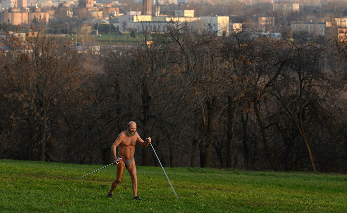 Мужчина в жару занимается скандинавской ходьбой