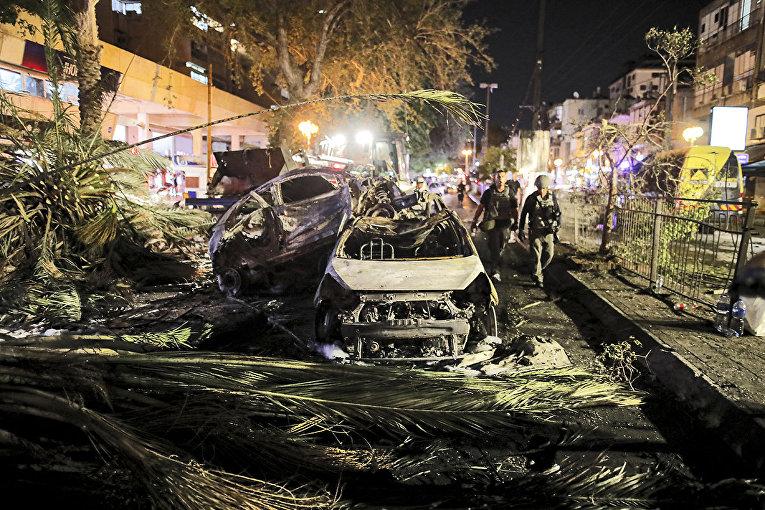 Автомобили, сгоревшие в результате ракетного обстрела в городе Холон в пригороде Тель-Авива