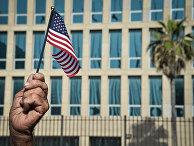 Американский флаг в руке кубинца у посольства США в Гаване
