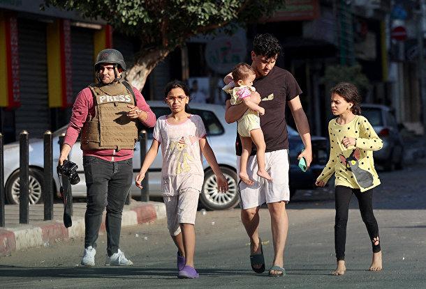 Палестинцы покидают свои дома после получения предупреждений израильской армии о том, что их здание будет подвергнуто авиаудару в секторе Газа