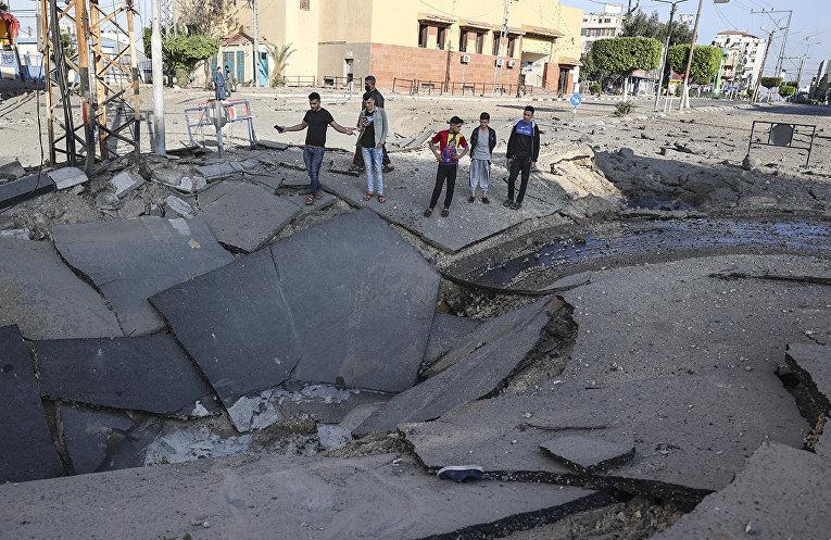 Палестинская молодежь фотографирует огромный кратер в секторе Газа