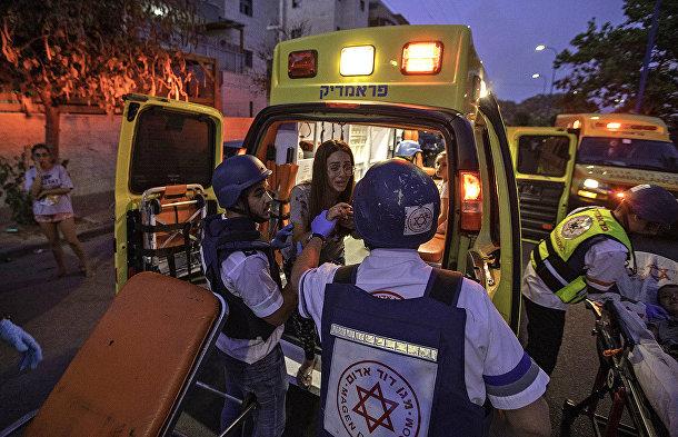 Спасатели эвакуируют женщину во время ракетного обстрела в Сдероте, Израиль