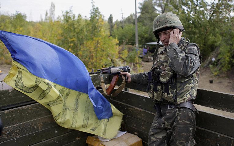 Украинский военнослужащий разговаривает по мобильному телефону на позиции вблизи города Первомайск Луганской области