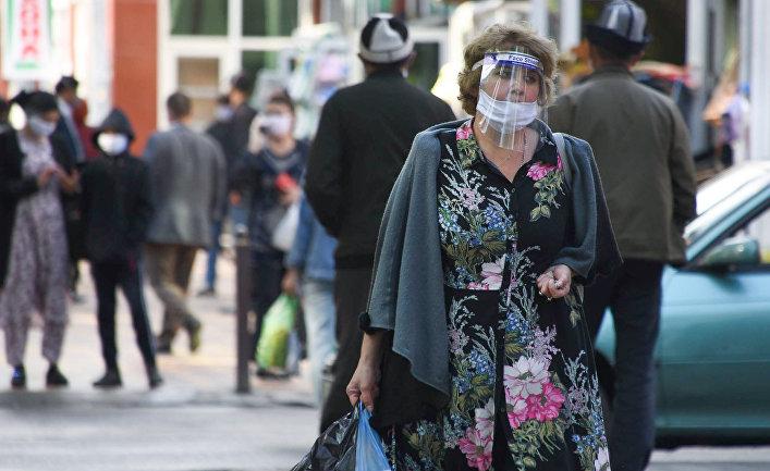 Женщина в защитной маске на одной из улиц в Душанбе