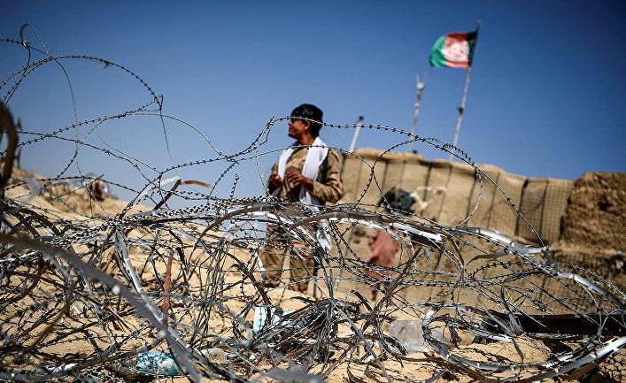 Полицейский у заставы, созданной против боевиков Талибана* в деревне Азиз Абад, Афганистан