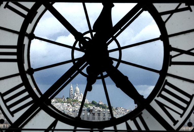 Вид на базилику Сакре-Кёр через гигантские часы музея Орсе в Париже
