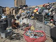 Афганец разбирает мусор, оставленный войсками США и НАТО